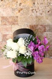 Yuvarlak kutuda mor orkide ve beyaz güller ile hazırlanan özel tasarım sevdiğinizi çok ama çok mutlu edecektir. Yaklaşık Ürün Boyutu: 25 cm