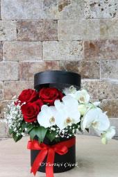 Kırmızı güller ve beyaz orkide ile hazırlanan aranjman ile kutuda çiçeklerin en güzelini sevdiğinize gönderin. Yaklaşık Ürün Boyutu: 25 cm