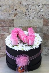 Yuvarlak silindir kutu içerisinde papatyalar üzerine pembe güller ile hazırlanan tasarım, her anınıza mutluluk katacaktır.